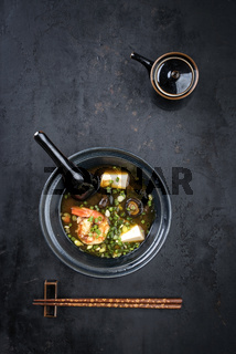 Traditional Japanese miso soup with king prawns and tofu as top view in a bowl with copy space