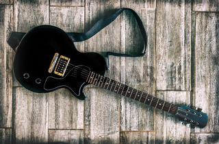 electric guitar grunge look studio shot up view on wooden background