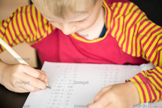 Young boy doing math homework for school at home