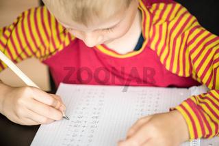 Junge beim Lösen von Mathematikaufgaben
