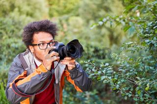 Junger Fotograf mit digitaler Kamera als Paparazzo