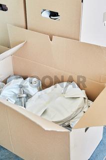 Zerbrechliche Gegenstände in Seidenpapier eingewickelt in einem Umzugskarton