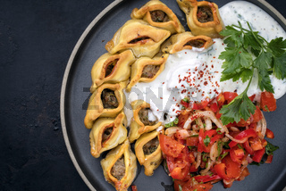 Traditional Armenian manti with mincemeat and paprika tomato salad as top view on a plate with copy space left
