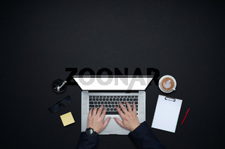 Businessman hands working with laptop . Flat lay and top view with office supplies and copy space on black background