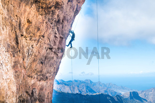Rock climber climbing up overhanging cliff