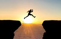 Man jumping over abyss in front of sunset.