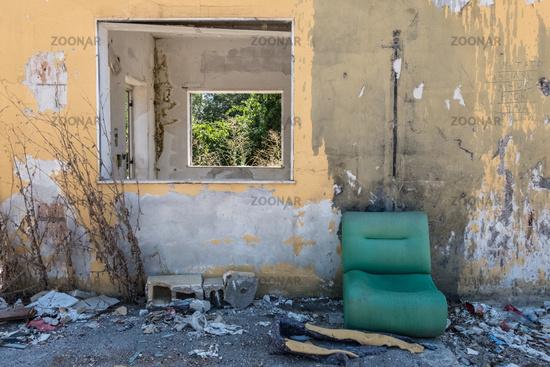 Abandoned worn facility with green shabby sofa.
