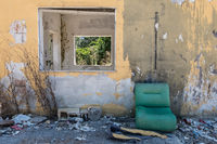 Abandoned worn facility with green shabby sofa.