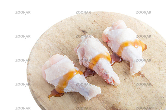 raw chicken legs on wooden cutting boards on white background