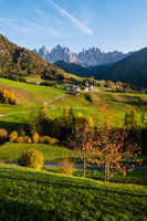 Autumn evening Santa Magdalena famous Italy Dolomites village view in front of the Geisler or Odle Dolomites mountain rocks. Picturesque traveling and countryside beauty concept background.