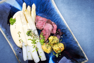 Modern barbecue dry aged sliced fillet steak with white asparagus in hollandaise sauce and roast potatoes as top view on a plate with copy space right
