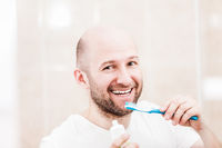 Smiling bald man holding toothbrush with toothpaste and brushing teeth