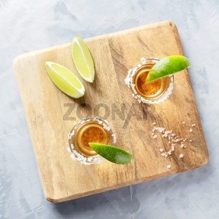 Golden tequila shots with lime slices and salt rims, overhead square shot