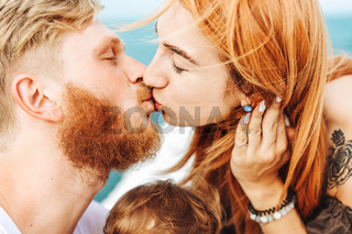Mom and Dad kiss. Happy family on vacation