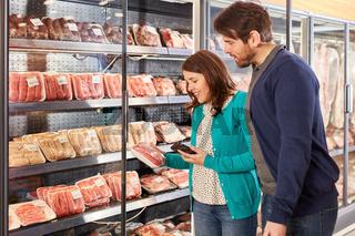 Paar schaut auf eine Packung mit Fleisch