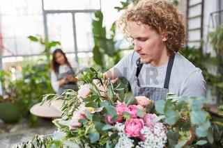 Florist mit Blumenschere beim Blumenstrauß kürzen