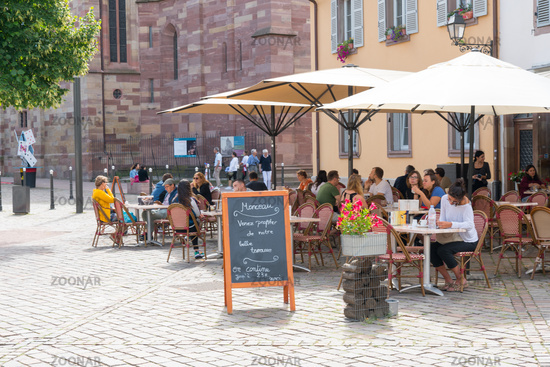 people enjoying drinks in French cafe outside of Saint Thomas' Church in the old city center of Stra
