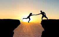 Man reaching hand to woman jumping over abyss in front of sunset.