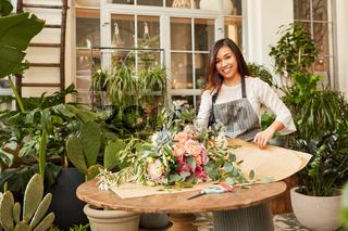 Junge Floristin wickelt großen Blumenstrauß ein