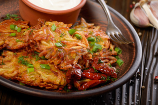 Closeup view at Homemade tasty potato pancakes in clay dish with sun-dried tomatoes and sour creram