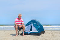 Man camping in shelter at the beach