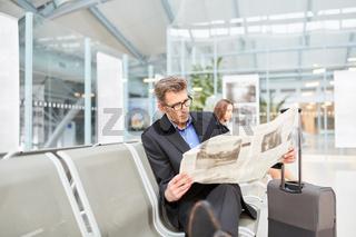 Business Mann liest Zeitung vor seiner Dienstreise