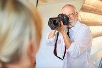Älterer Fotograf mit Kamera macht Porträtfotos