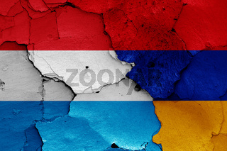 flags of Luxembourg and Armenia painted on cracked wall