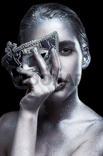 Female with masquerade venecian mask in hand near face. Silver girl on black background