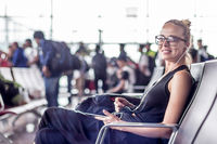 Female traveler using her cell phone while waiting to board a plane at departure gates at asian airport terminal.