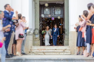 Newlyweds exiting the church after the wedding ceremony, family and friends celebrating their love with the shower of soap bubbles, custom undermining traditional rice bath