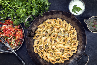 Traditional Armenian manti with mincemeat and paprika salad as top view in a cast iron pan