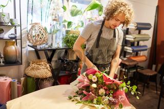 Junger Mann als Florist bindet einen Blumenstrauß