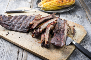Barbecue spare ribs St Louis cut with hot rub and corn as closeup on a wooden cutting board