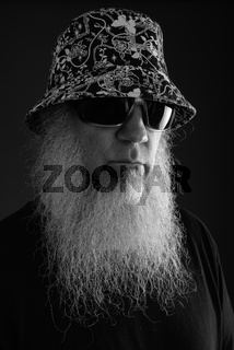 Mature man with long beard against gray background in black and