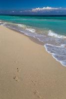 Footprints on a tropical white sand beach
