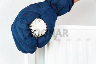 Hand in glove turns heating valve in winter