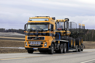Yellow Volvo FH Truck Hauls Ponsse Forestry Equipment