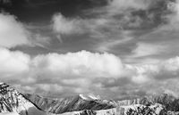 Panorama of snowy mountains and sky with sunlit clouds