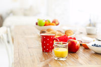 Coffee with fruit, cereal and croissant on wooden table background