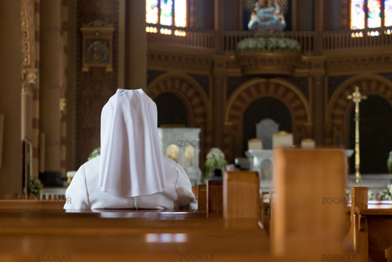 A nun in traditional white robes meditates in a Christian cathedral.