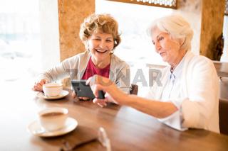 Excited old ladies watching video on smartphone