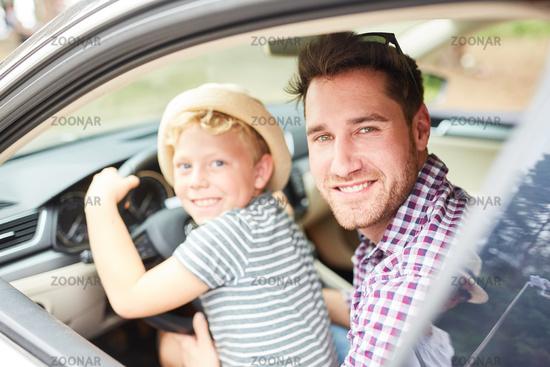Kleiner Junge sitzt am Lenkrad im Auto
