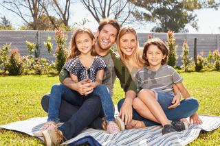 Glückliche Familie mit zwei Kindern sitzt im Garten