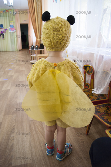 A three-year-old child, a sad blond boy with blue eyes, in a bee costume