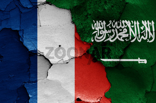 flags of France and Saudi Arabia painted on cracked wall