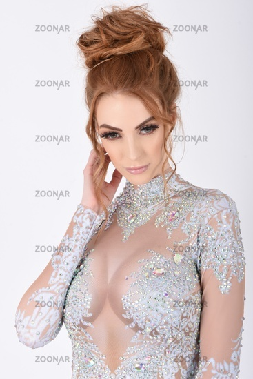 Sexy, tall, busty Redhead dressed in a white see-through glitter Bodysuit
