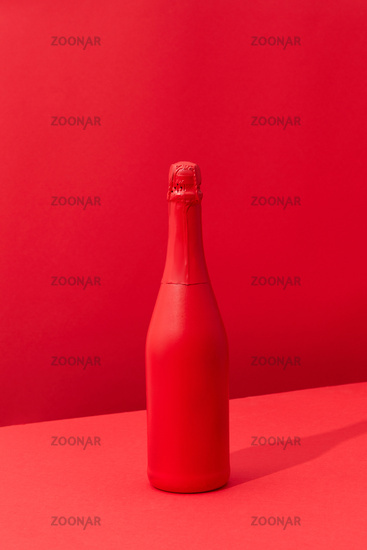 Red painted spray wine bottle on a duotone red background.