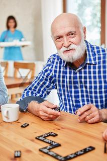 Senior mit Alzheimer beim Domino spielen