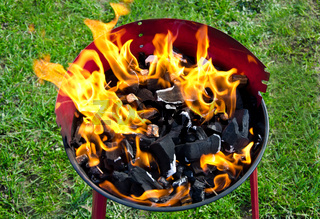 Flames and coal on a barbecue grill in summer
